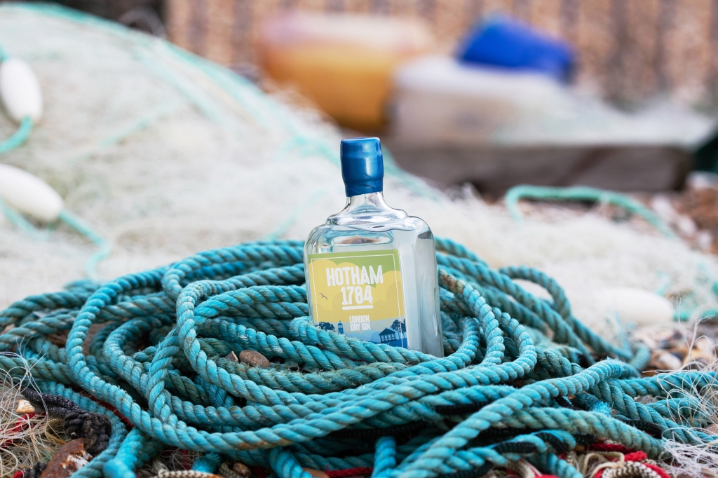 Photograph of a 1784 Gin bottle wrapped in blue rope. Taken by GS Creative Photography on Bognor Regis beach